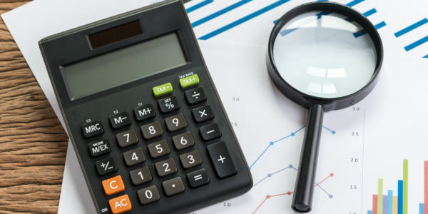 Business perfomance review or KPI key point indicator estimation concept, calculator with magnifier glass on pile of graph and chart performance print paper on wood table.